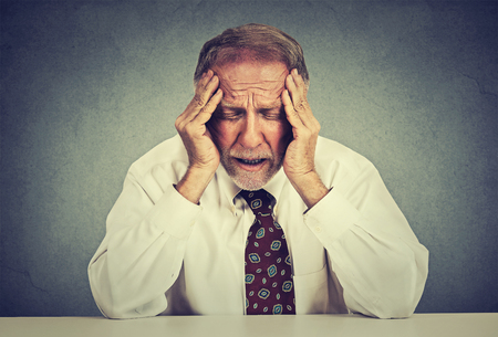 remorse: Stressed hopeless elderly business man in depression sitting at the office table isolated on gray wall background. Overworked worried senior employee