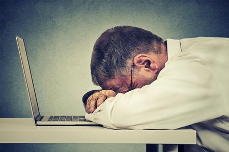 dormir: Perfil lateral maduro hombre de negocios que duerme en una computadora portátil aislados sobre fondo gris de la pared de la oficina. La privación del sueño, horas de trabajo concepto larga