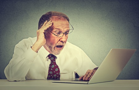 offended: Closeup portrait anxious senior man looking at laptop screen seeing bad news or photos with disgusting emotion on his face isolated on gray office wall background. Human emotion, reaction, expression