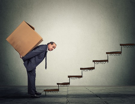 difficult task: Difficult task challenge concept. Middle aged business man carrying large heavy box on his back upstairs