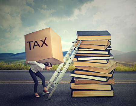 financial burden: Tax debt concept. Young woman professional with heavy box full of tax debt carrying it up the career ladder