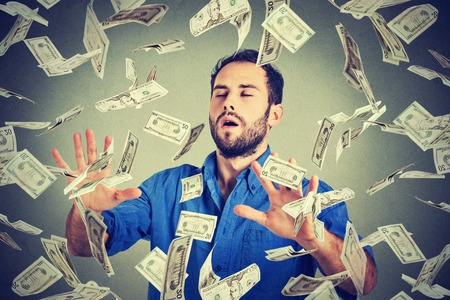 business money: Young entrepreneur business man with eyes closed trying to catch dollar bills banknotes flying in air walking through money rain gray background. Financial corporate success crisis challenge concept Stock Photo
