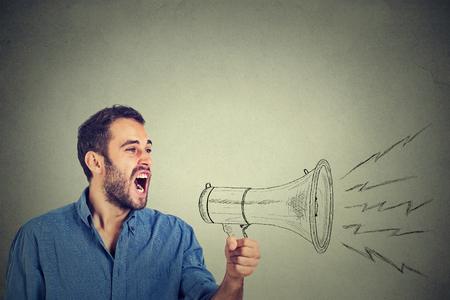 merken: Side Porträt zorniger junger Mann, der schreiend in Megaphon isoliert grauen Hintergrund. Negative Gesicht Ausdruck Gefühl Gefühl. Propaganda, Nachrichten, Macht, Social-Media-Kommunikationskonzept