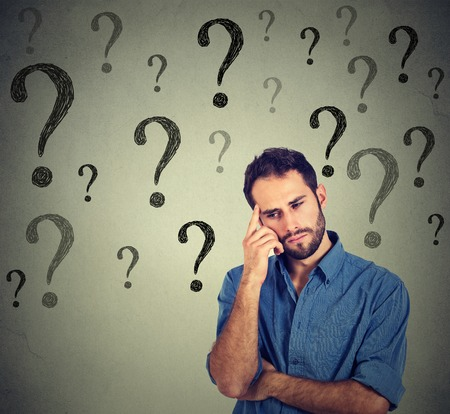preguntando: Pensar apuesto joven hombre de negocios preguntándose mirando hacia abajo tiene muchas preguntas aisladas en el fondo de la pared gris con muchos signos de interrogación. Chico Pensando Foto de archivo