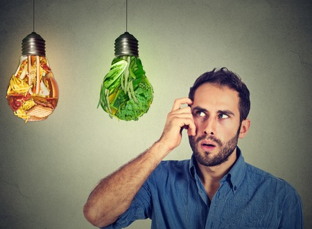 mente humana: Desconcertado hombre de pensamiento que mira hacia la comida chatarra y los vegetales verdes como forma de bombillas de toma de decisiones aisladas sobre fondo gris. Dieta elección correcta nutrición estilo de vida saludable concepto de bienestar