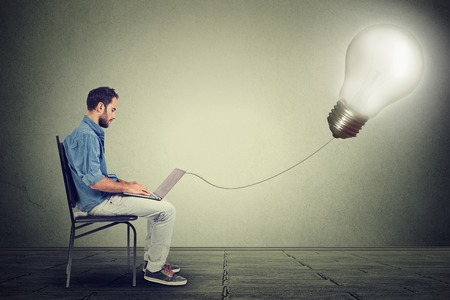 plugged in': Young professional man using a laptop with light bulb plugged in it isolated on gray wall background
