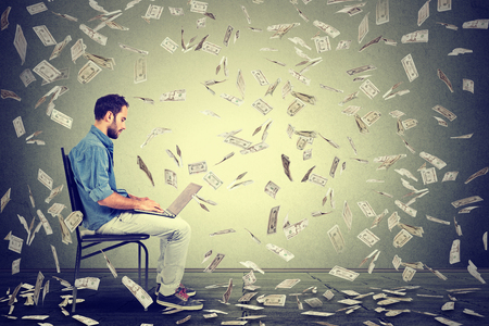 Jonge man met behulp van een laptop gebouw online bedrijf maken van geld dollarbiljetten contant geld vallen. Geld regen beginner IT ondernemer succes economie concept