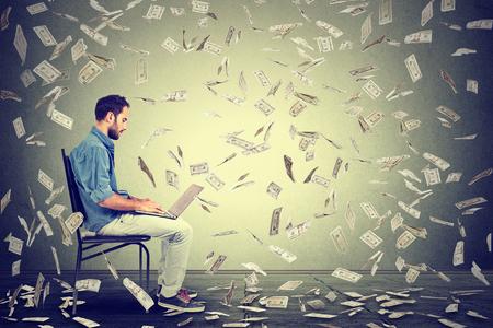 Young man using a laptop building online business making money dollar bills cash falling down. Money rain beginner IT entrepreneur success economy concept