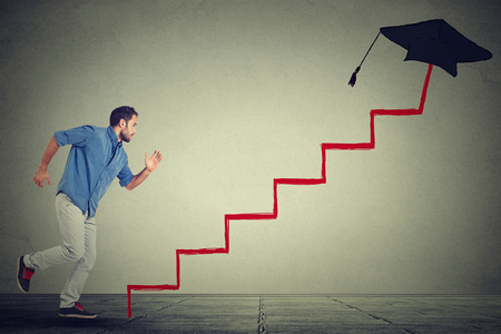 Concetto di progresso bersaglio istruzione. Giovane studente uomo correre su scala istruzione professionale