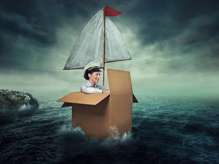 Vrouw reizen door water. Geluk vrijheid. Gelukkig lachende jonge vrouwelijke kapitein ondernemer. Ontworpen denkbeeldige schip gemaakt van kartonnen doos
