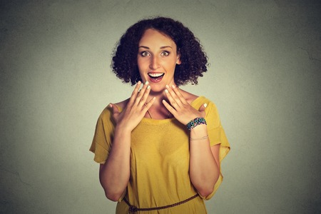 woman chest: Closeup portrait of happy cute young woman looking excited, surprised in full disbelief, hands on chest, its me? isolated on gray background. Positive human emotions, facial expression reaction Stock Photo