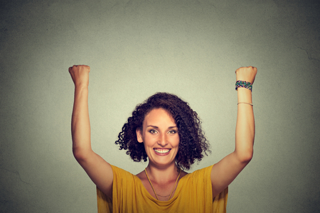 Successful woman with arms up celebrating Imagens