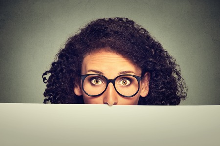 latina girl: Banner sign woman in glasses peeking over edge of blank empty paper billboard. Beautiful young woman with glasses looking surprised and scared funny with wide open eyes isolated on grey background Stock Photo