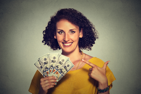 feeling happy: Closeup portrait super happy excited successful young business woman holding money dollar bills in hand isolated grey wall background. Positive emotion facial expression feeling. Financial reward
