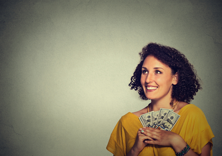 financial reward: Closeup portrait happy excited successful young business woman holding money dollar bills in hand looking up isolated grey wall background. Positive emotion facial expression feeling. Financial reward
