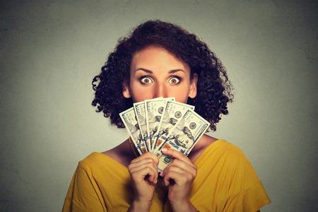 Scared uitziende vrouw ondergedoken plukken door middel van dollar biljetten Stockfoto