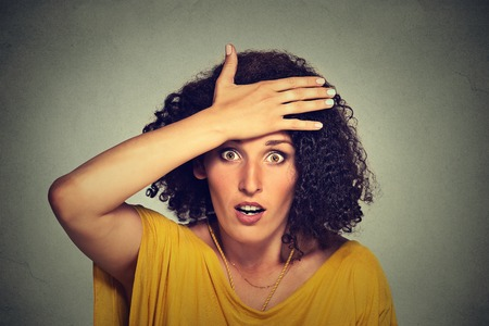 in the mouth: Concerned scared shocked woman with hand on forehead gesture