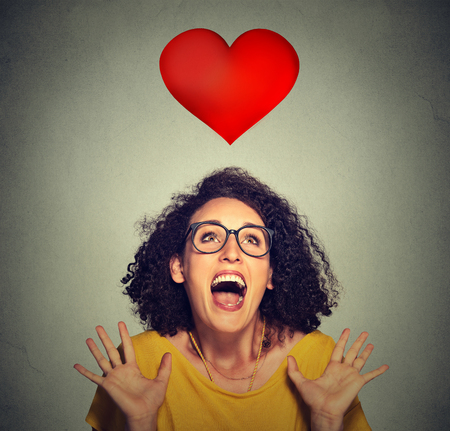 funny glasses: portrait super excited funky girl in love looking up at red heart isolated on grey wall background