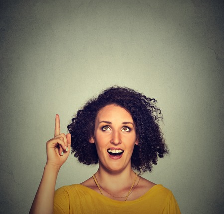 aha: Portrait happy beautiful woman with idea looking up pointing with finger at blank copy space isolated gray background. Positive human face expression emotion feeling body language perception
