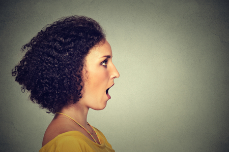 english girl: Closeup side view profile portrait woman talking with sound coming out of her open mouth isolated grey wall background. Human face expression emotions. Communication, information, intelligence concept