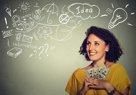 financial reward: Closeup portrait happy excited successful young business woman holding money dollar bills in hand isolated grey wall background with info graphics. Positive emotion facial expression. Financial reward