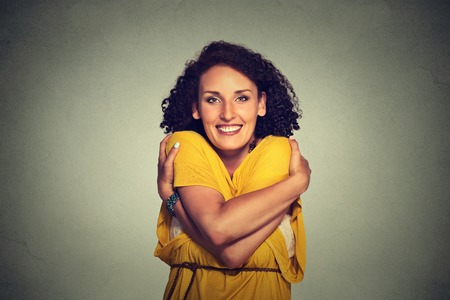Closeup portrait happy smiling woman holding hugging herself isolated on grey wall background. Positive human emotion, facial expression, feeling, reaction, situation, attitude. Love yourself concept