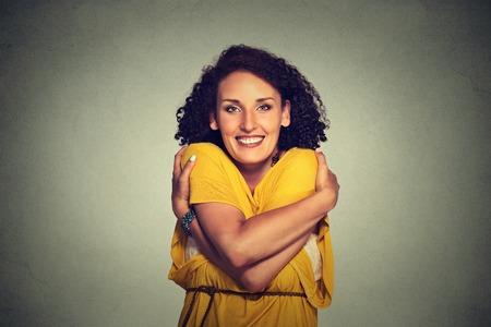 mujer trabajadora: Mujer sonriente Primer retrato feliz celebraci�n abraz�ndose aislados sobre fondo gris de la pared. Emoci�n positiva humana, la expresi�n facial, sensaci�n, reacci�n, situaci�n, actitud. �mate a ti mismo concepto