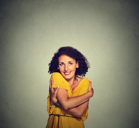 donna innamorata: Ritratto del primo piano felice donna sorridente azienda che si abbraccia isolato su sfondo grigio muro. Emozione positiva umana, espressione del viso, sensazione, reazione, situazione, l'atteggiamento. Amare se stessi concetto Archivio Fotografico