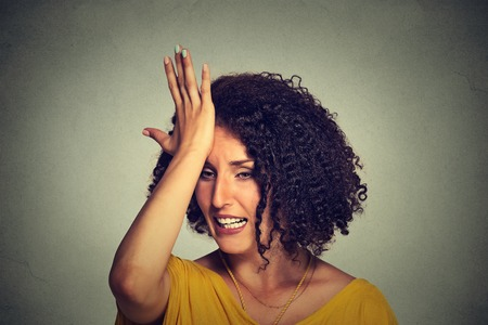 Closeup portrait middle age woman slapping hand on head to say duh made mistake isolated on gray background. Negative human emotion facial expression feelings, body language Stock Photo