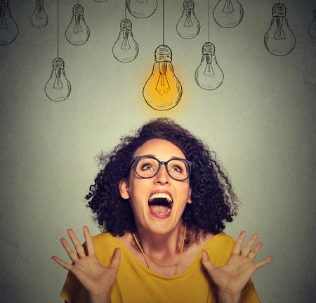 niña pensando: Retrato super feliz mujer emocionada en vidrios que miran para arriba brillante idea bombilla encima de la cabeza aislada en el fondo de la pared gris