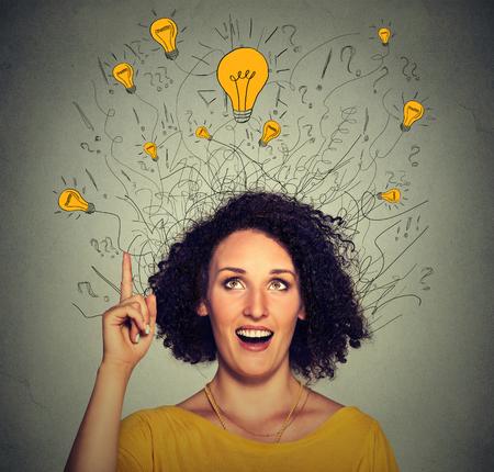 bombillo: Mujer emocionada primer con muchas ideas Bombillas sobre la cabeza mirando hacia arriba apuntando el dedo hacia arriba aislados sobre fondo gris de la pared. Eureka concepto de la creatividad