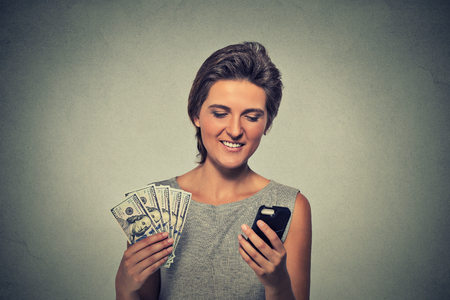 users video: Excited woman with smart phone and dollar banknotes isolated on gray wall background
