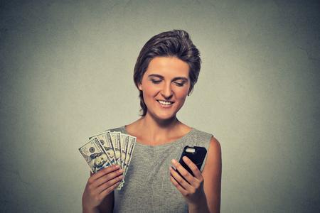 cash money: Mujer emocionada con el teléfono inteligente y el dólar billetes de banco aislado en el fondo de la pared gris Foto de archivo