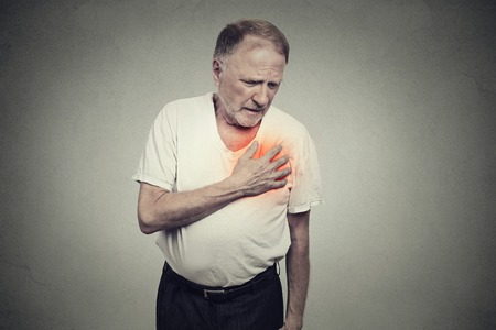 breath: senior man suffering from bad pain in his chest heart attack isolated on gray background
