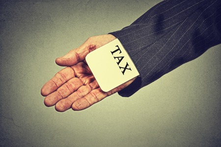 impuestos: Corrupción concepto penal ilegal impuesto actividad esquema ponzi economía evasión. Tarjeta de impuestos escondite hombre de la mano del primer en una manga de un traje aislado sobre fondo gris de la pared