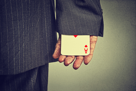 conman: Closeup cropped image man hand pulling out a hidden ace from the sleeve isolated on gray wall background Stock Photo