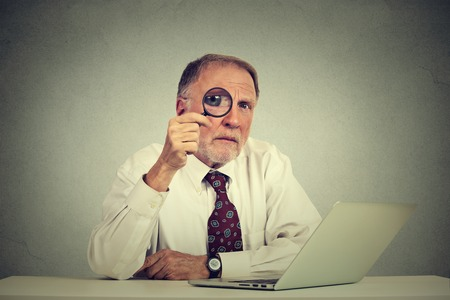 cynical: Serious business man in glasses skeptically looking through magnifying glass at you sitting at office table with laptop computer isolated gray background. Human face expression attitude, perception Stock Photo