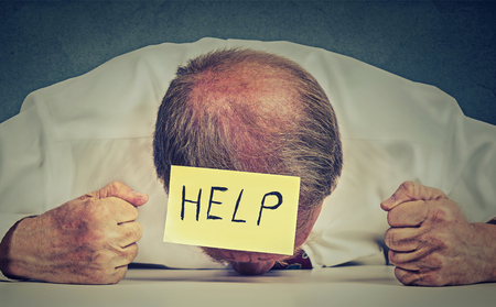 working hours: Tired, stressed senior employee needs help. Frustrated elderly man with note on his forehead leaning his head on the table exhausted. Long working hours, aging concept