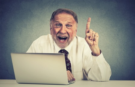 elearn: Portrait excited senior man using laptop computer has an idea isolated on gray wall background Stock Photo