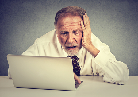 network people: Portrait senior stressed man working on laptop sitting at table isolated on gray wall background Stock Photo