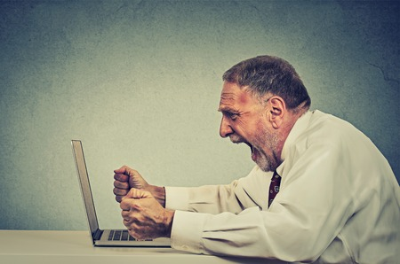 stress management: Angry furious senior business man working on computer, screaming. Negative human emotion facial expression feeling aggression anger management issues concept. Side profile guy having nervous breakdown Stock Photo