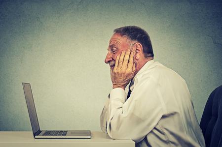 ergonomics: Senior man using laptop computer reading email news. E-learning concept Stock Photo