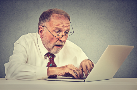 internet search: Confused surprised senior man using a pc laptop computer Stock Photo