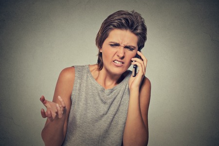 upset: Upset skeptical, unhappy angry woman talking on phone isolated on gray background. Negative human emotion facial expression feeling, life reaction. Bad news