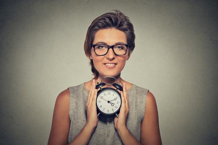 punctuality: mujer sonriente joven con despertador aislado fondo de la pared gris. Expresi�n de la cara humana. El tiempo, la puntualidad, la apretada agenda concepto