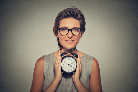 punctuality: young smiling woman with alarm clock isolated grey wall background. Human face expression. Time, punctuality, busy schedule concept
