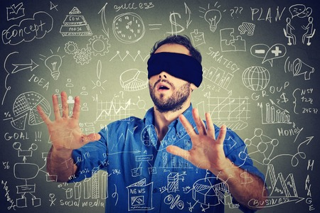 intuition: Blindfolded young business man searching walking through complicated social media financial data plan. Sightless entrepreneur analyst managing corporate unknown economy risk concept