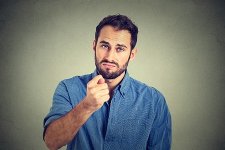 deny: Man giving thumb, finger figa gesture you get zero nothing isolated on grey background. Human emotions, facial expressions, feeling, body language