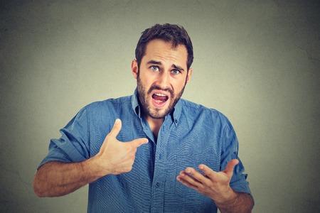 conflicto: Primer retrato de hombre enojado, infeliz joven apuntando a sí mismo pidiendo que me quieres decir, que hablar conmigo, aislado sobre fondo gris. Emoción humana Negativo sentimiento expresión facial