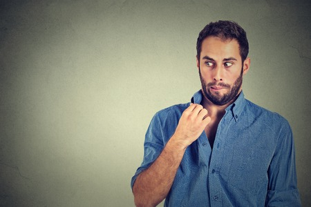 man face: Closeup portrait, young man opening shirt to vent, its hot, unpleasant, Awkward Situation, Embarrassment. Isolated on gray background. Negative emotions facial expression, feelings